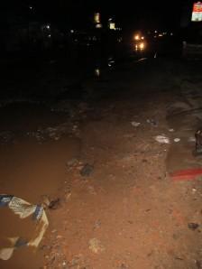 The water-laden, pothole-strewn mess outside Sidewalk Never Die Hotel.