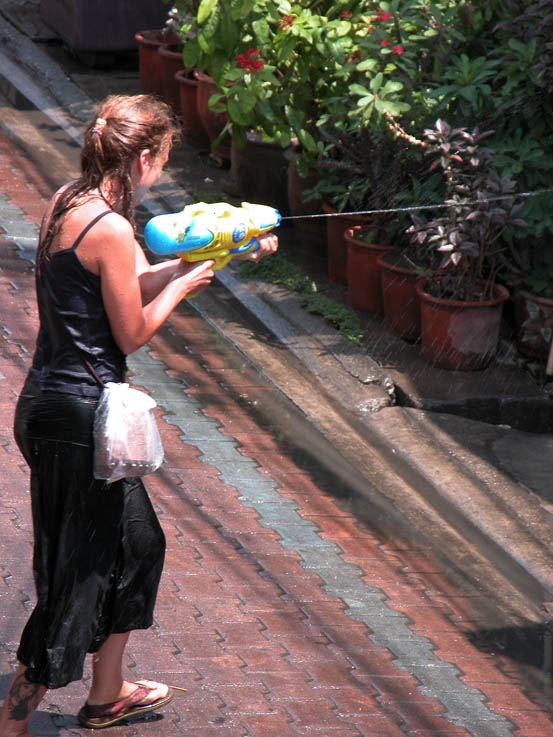 A mum shows her son how it's done at Songkran.