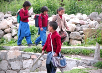 Kids coming home from school, carrying their slates, which are still used up in these parts. On the right you can see a 'Debta' post - very strong magic. Chitkul.