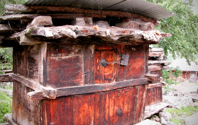A storehouse with an old padlock on one of its small doors. Each family has a storehouse of their own. Chitkul.