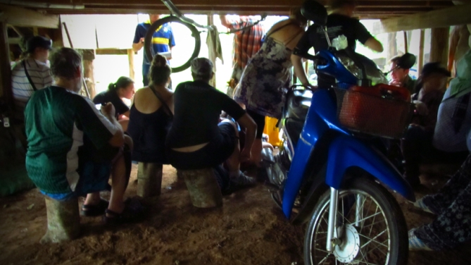 Volunteers, motorbikes, dogs and chickens all await the passing of the thunderstorm under a local house.