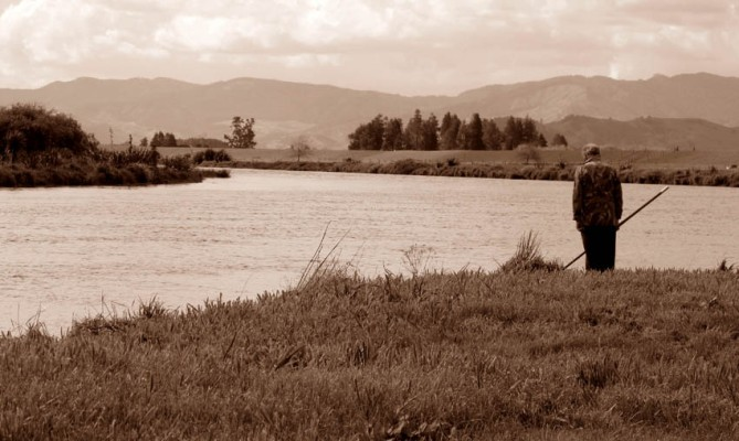 Fishing - favourite pastime of many a Kiwi bloke. I strongly suspect that in many cases it's used as a fairly legitimate excuse to get out of the house... Looking towards the mountain ranges on the way to Thames, from the Hauraki Plains. Coromandel Peninsula, North Island.